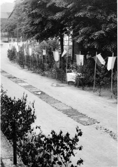 Die große Prozession in Mülheim - Festliche Blumenteppiche und Fahnen schmücken die Von-Plettenberg-Straße in den 1950er Jahren vor dem Haus der Familie Arens. Anlass ist die große Prozession am Sonntag nach dem Fest Mariä Heimsuchung, wel-ches am 2. Juli gefeiert wird. Die große Prozession war eine alte Tradition im Kirchspiel, die sich wahrscheinlich auf die Zeit des dreißigjährigen Krieges und auf heidnische Bräuche zurückführen lässt. Ein Zusammenhang mit dem Bau der Kapelle 1625 in Waldhausen ist auch denkbar. Die aufwändigen Prozessionen wurden bis in die siebziger Jahre des letzten Jahrhunderts durchgeführt. Danach wurde diese Tradition nicht weiter verfolgt.