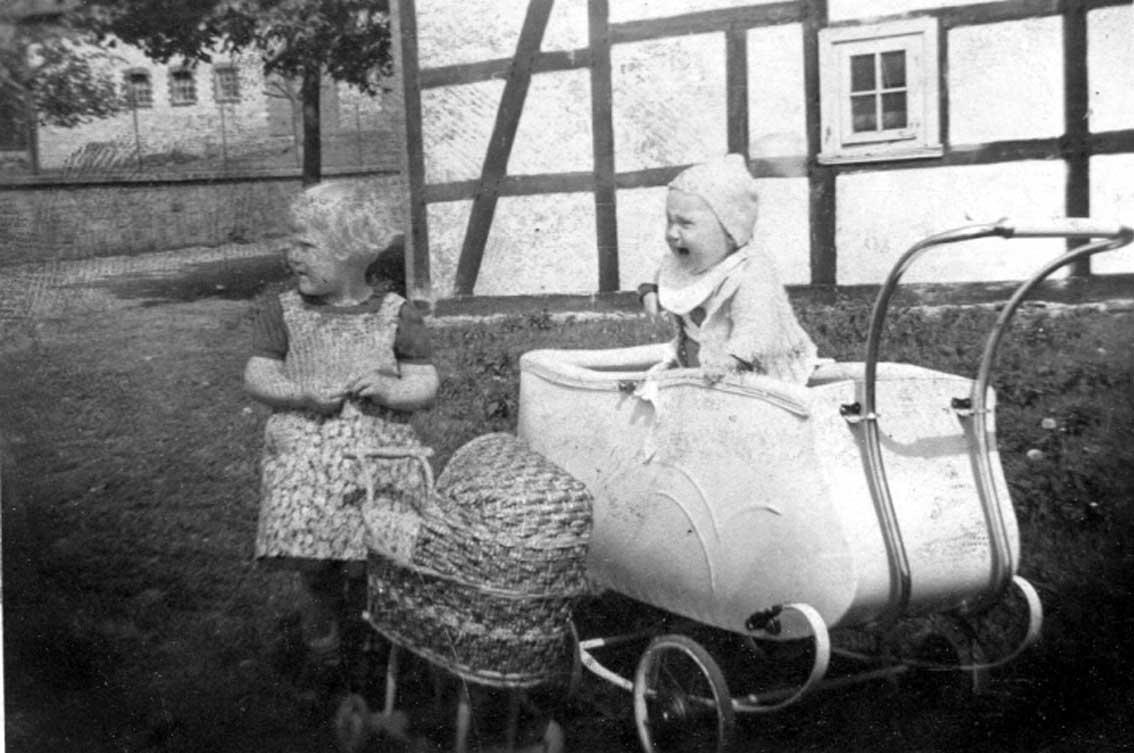 Kinderalltag in Mülheim / Um 1941 sieht man hier die Geschwister Elisabeth und Theo Arens. Während Elisabeth als stolze Puppenmutti ihren geflochtenen Korb-Puppenwagen gerade geparkt hat, scheint ihr kleiner Bruder, stehend im Cabrio-Kinderwagen, mit irgendetwas so gar nicht einverstanden zu sein. Im Hintergrund links erkennt man Korffs Stall, rechts Micheln Fachwerkhaus an der Möhnestraße in Mülheim.