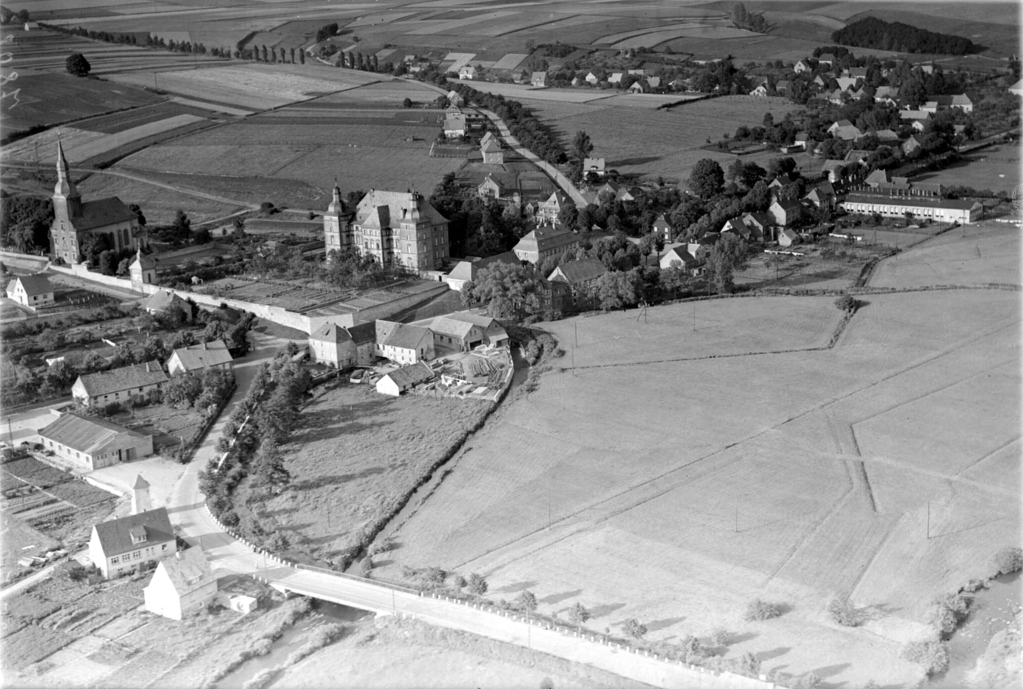 """Das Luftbild aus dem Jahr 1952 mit Blickrichtung Nord-Ost bietet einen sehr guten Überblick über Sichtigvor. Der """"Damm"""" ist hier« noch in seiner ursprünglichen Form mit einer Böschung nach Westen erkennbar. An der Einmündung Jahnstraße - St.Georg-Straße ist noch das alte Stromhäuschen vor der Halle der Familie Richter zu erkennen. Auf den Möhnewiesen ist der ehemalige Fußweg von der Römerstraße zur Mühle schwach sichtbar. Die Gärten des Schlosses Mülheim zeigen sich in ihrer vollen Pracht im Zentrum des Bildes. Die Neue-Straße ist zu diesem Zeitpunkt nur spärlich bebaut."""