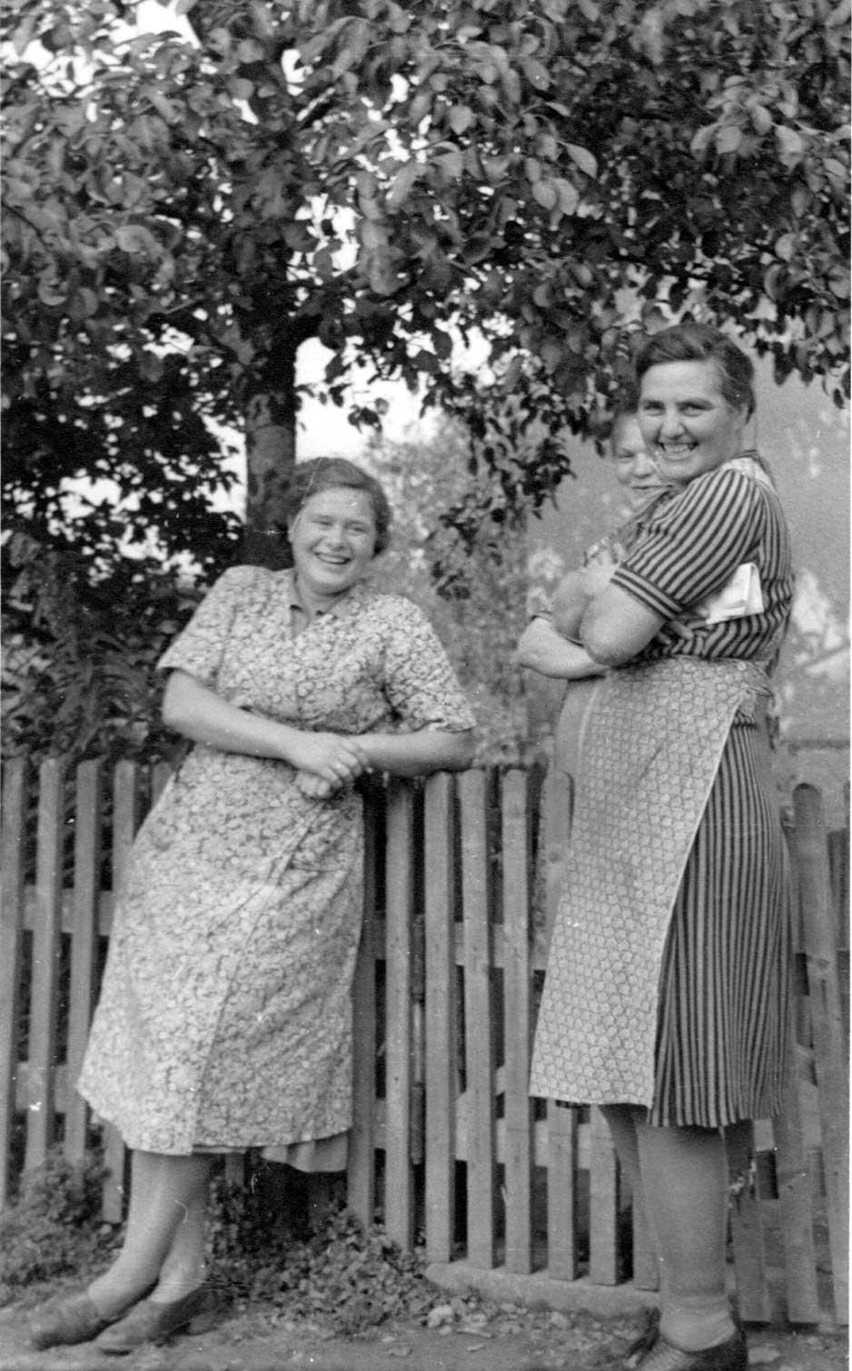 Ruhepause am Gartenzaun oder die Ruhe vor dem Sturm / Mitte der 1950 Jahre trugen die Frauen bei der Hausarbeit noch durchweg Schürzen oder Kittelschürzen. Drei gestandene Hausfrauen, Thea Kemper, Thea Schöne und dahinter Frau Bergmann haben sich zu einem kurzen Plausch am Zaun vor dem Haus bei Schmidt Holtknecht an der St.- Georg - Straße getroffen. Das Mittagessen steht schon auf dem Herd - gleich werden die Ehemänner zur Mittagspause kommen.