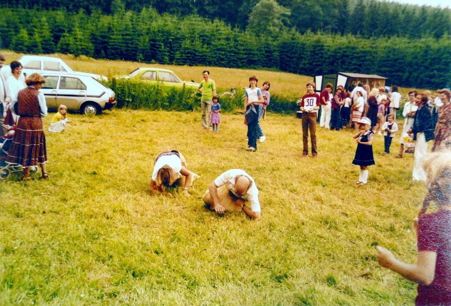 """Das Waldfest am Erlenbruch – Großer Beliebtheit erfreute sich lange Jahre das """"Waldfest"""" am Erlenbruch, welches dort bis 1987 jährlich von der Kolpingfamilie und dem Musikverein Sichtigvor ausgerichtet wurde. Besonderen Spaß bereitete es immer allen, wenn sich die """"Großen"""" bei den Spielen für die """"Kleinen"""", wie hier beim Sackhüpfen, einen Wettkampf lieferten. Nachdem man vom Erlenbruch umziehen musste, fand das Fest noch bis 2005 als """"Mühlenfest"""" im Mühlenpark statt."""