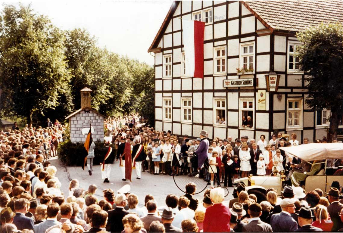 Großer Festumzug zum Dorfjubiläum Mülheim - Anlässlich der 900 Jahrfeier Mülheims wurde 1972 ein großer Festumzug durch Mülheim und Sichtigvor veranstaltet. Gut zu erkennen sind Willi Eickhoff auf seinem Hochrad und die Fahnenabordnungen des Kolping- und Josefsvereins. Der Festumzug befindet sich auf dem Weg zum Haus Teiplaß in der Höhe vom Gasthof Schöne. Dieses ortsbildprägende Gebäude wurde 2014 abgerissen. Seit 2018 steht dort das Seniorenzentrum Möhnetal.