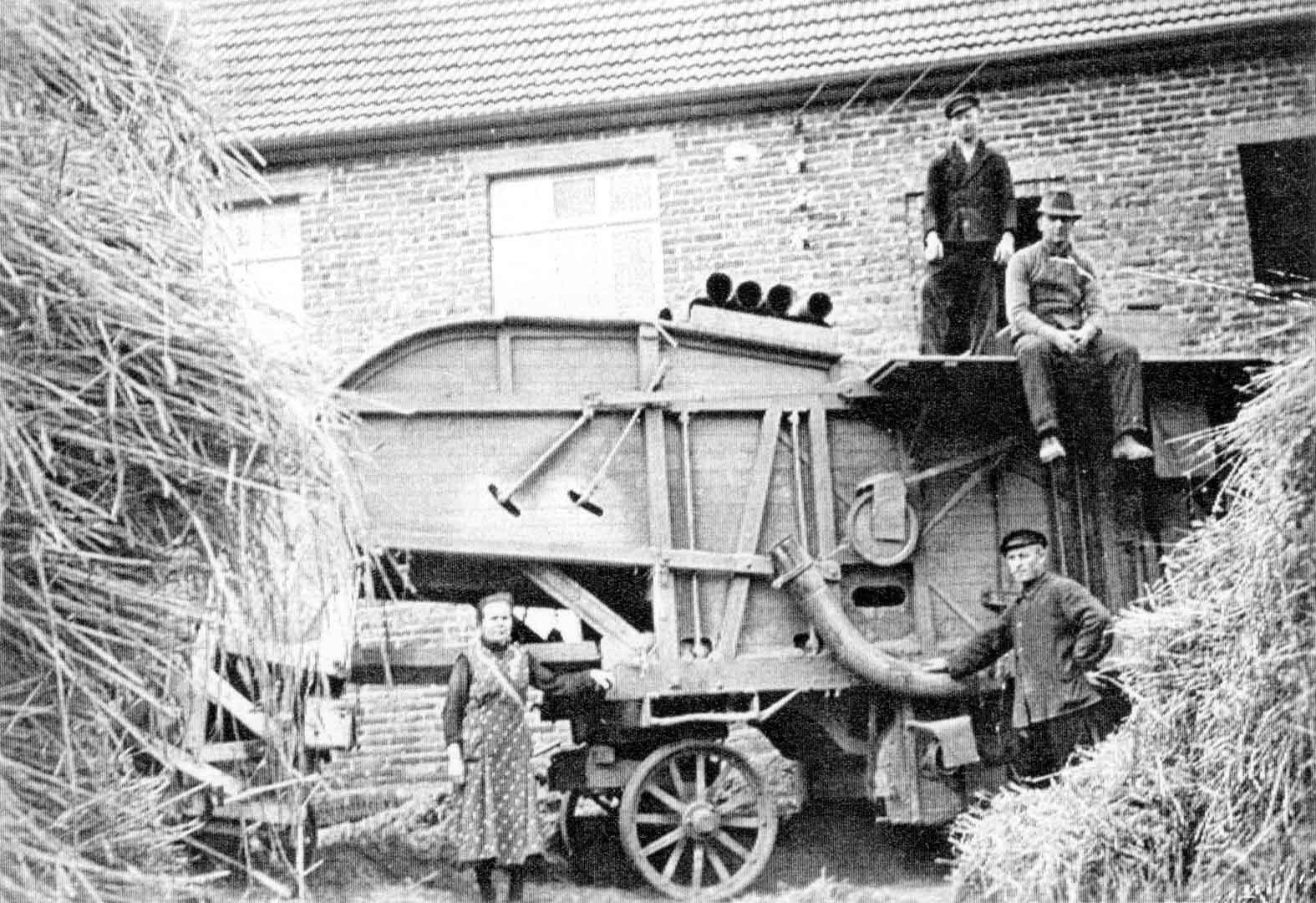 Die Arbeit ist getan - Der schwere Dreschkasten vor dem Haus Pankoke in Waldhausen ist bereit, zum nächsten Einsatz gefahren zu werden. Die Rohre für das Kaffgebläse sind für den Transport gut befestigt. Den Leuten ist die Erleichterung nach getaner schwerer Arbeit anzusehen. Wir erkennen auf diesem Bild um 1950 Hubert Pankoke mit seiner Frau Bernhardine und Wilhelm Eickhoff auf der Maschine.
